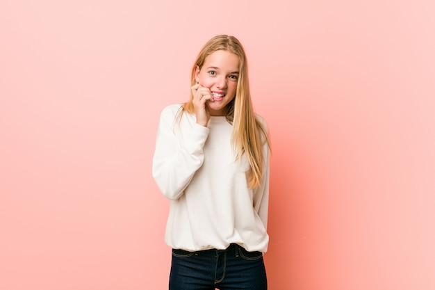 Młoda blondynka nastolatka gryząca paznokcie, nerwowa i bardzo niespokojna.