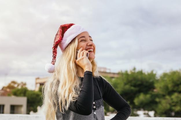 Młoda blondynka o boże narodzenie rozmowa telefoniczna śmiejąc się i zabawy. boże narodzenie i koncepcja komunikacji