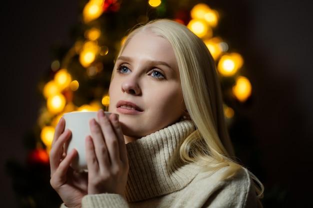 Młoda blondynka pije pachnące kakao w domu w pobliżu choinki.