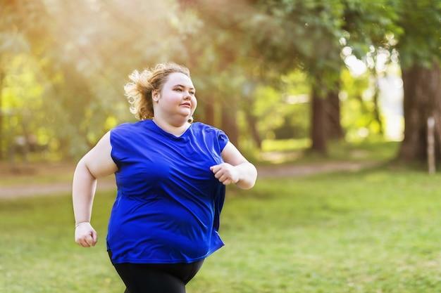 Młoda blondynka plus size biegnie w parku w słoneczny letni wieczór
