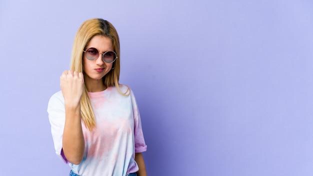 Młoda blondynka pokazuje pięść do przodu, agresywny wyraz twarzy