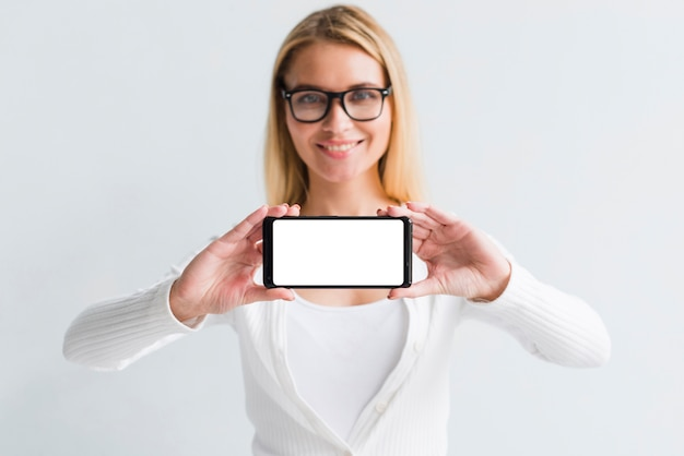 Młoda blondynka pokazuje smartphone ekran