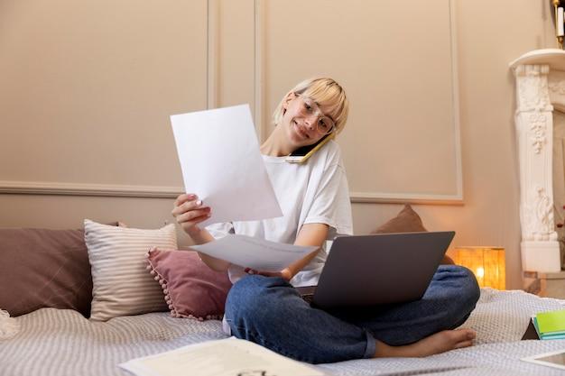 Młoda blondynka pracująca w domu w swoim łóżku