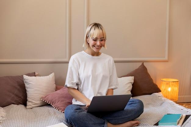 Młoda blondynka pracuje w domu na swoim laptopie