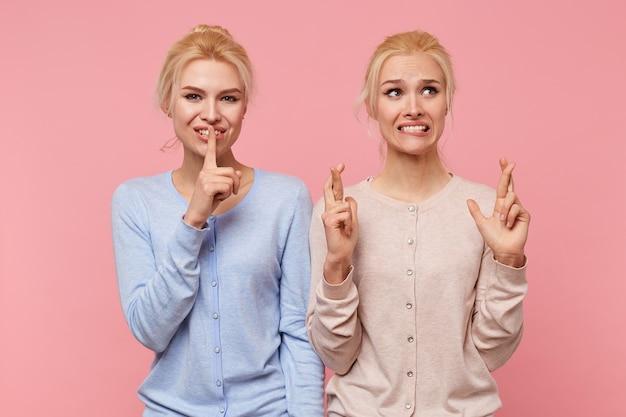 Młoda blondynka prosi o ciszę, aby jej siostra mogła wypowiedzieć życzenie na różowym tle.