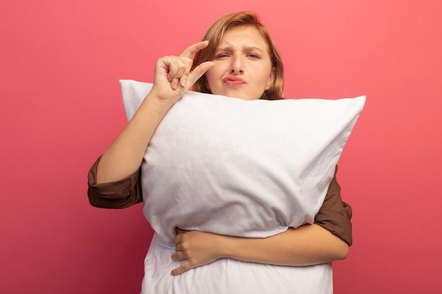 Młoda blondynka przytulająca poduszkę patrząca na mały gest na różowej ścianie