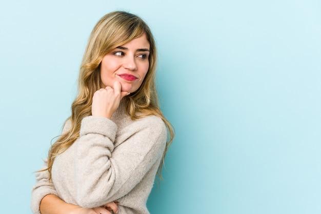 Młoda blondynka rasy kaukaskiej patrząc z ukosa z wyrazem wątpliwości i sceptycyzmu.
