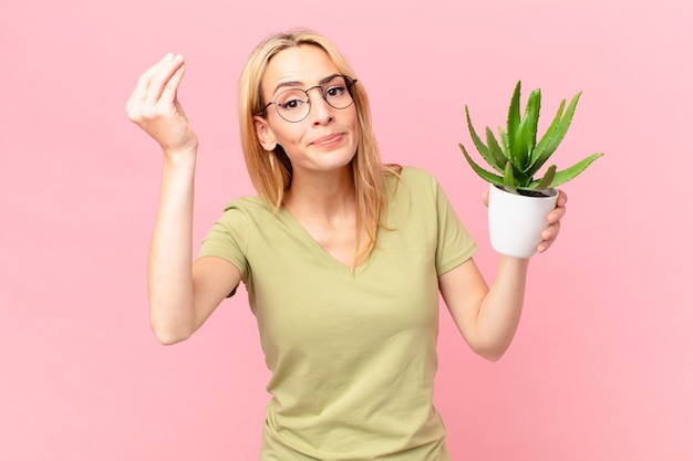 Młoda blondynka robi gest kaprysu lub pieniędzy, mówiąc, że masz zapłacić i trzyma kaktusa