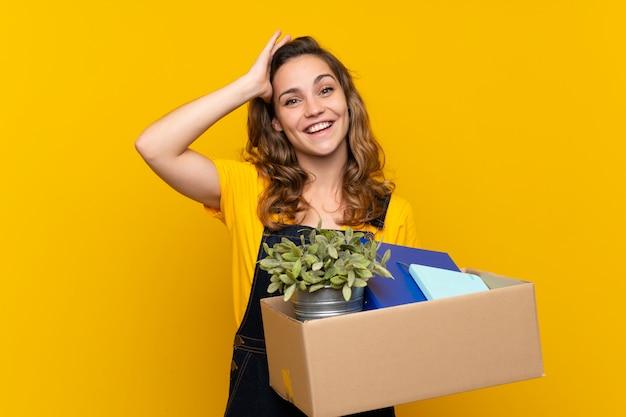 Młoda blondynka robi ruch, podnosząc pudełko pełne rzeczy z zaskoczeniem i zszokowanym wyrazem twarzy