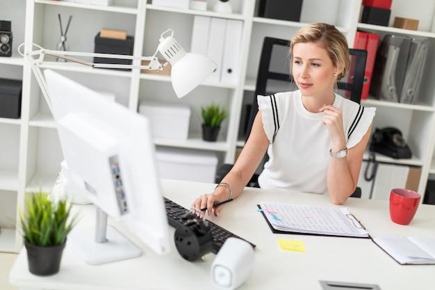 Młoda blondynka siedzi przy biurku komputerowym w biurze, trzyma ołówek w dłoni i drukuje na klawiaturze.
