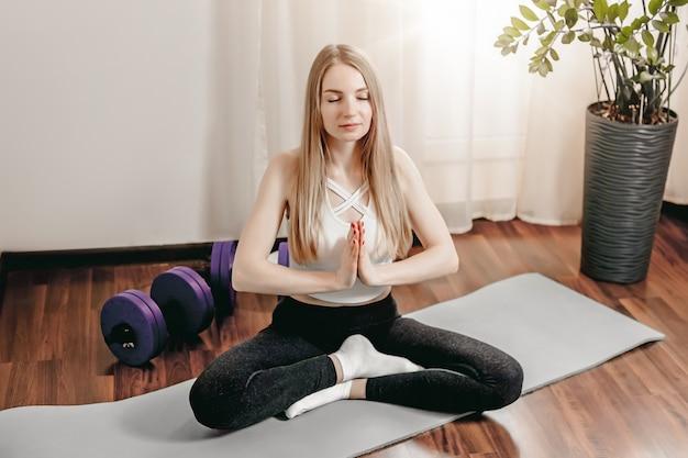 Młoda blondynka siedzi w pozycji lotosu z rękami założonymi na wysokości klatki piersiowej, z zamkniętymi oczami na macie do jogi i medytuje.