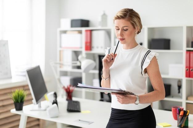 Młoda blondynka stoi przy stole w biurze i trzyma w rękach dokumenty oraz ołówek.