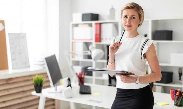 Młoda blondynka stoi w pobliżu stołu w biurze i trzyma dokumenty i ołówek w dłoniach.