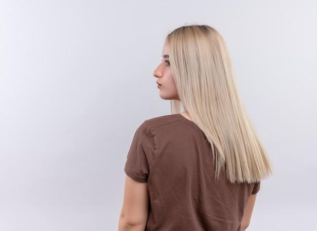 Młoda blondynka stoi z tyłu widok patrząc na lewą stronę na na białym tle białej ściany z miejsca na kopię