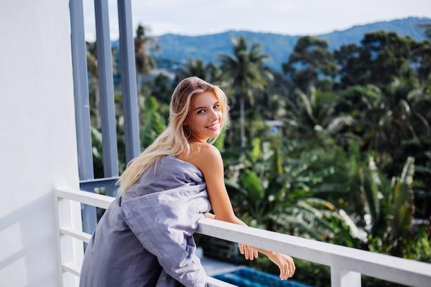 Młoda blondynka stylowa europejska kobieta w koc na tropikalnym balkonie spotyka wschód słońca.