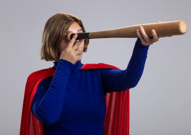 Młoda blondynka superbohatera w czerwonej pelerynie trzymając kij baseballowy, używając go jako teleskopu na białym tle
