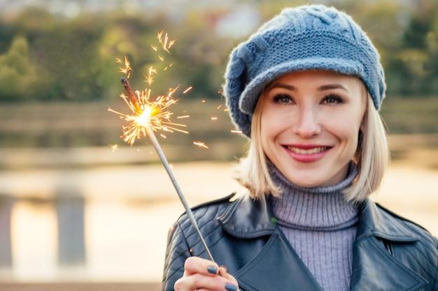 Młoda blondynka szczęśliwa uśmiechnięta kobieta w beżowym płaszczu i ciepłym kapeluszu z bengalskimi światłami w jej ręce odkryty portret zbliżenie w jesiennym parku. zimno na zewnątrz. zimowe ubrania wiosenne, boże narodzenie, koncepcja nowego roku
