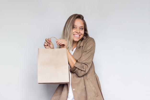 Młoda blondynka trzyma i pokazuje papierową eko torbę z pustym miejscem na logo