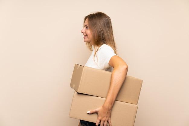 Młoda blondynka trzyma pudełko, aby przenieść je na inne miejsce w pozycji bocznej