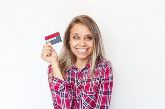 Młoda blondynka trzymająca w ręku plastikową kartę kredytową płatność za zakupy