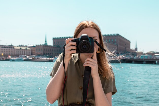 Młoda blondynka turis w lekkiej letniej sukience w zielonym kolorze khaki trzyma aparat fotografujący miasto, w tle wybrzeże morza sztokholmskiego w słoneczny dzień. koncepcja podróży podróży.