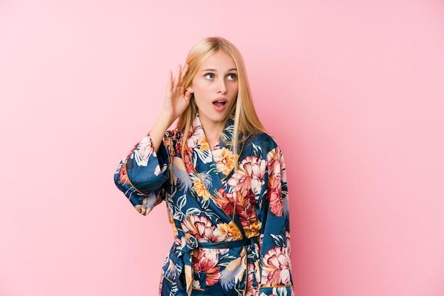 Młoda blondynka ubrana w piżamę kimono próbuje słuchać plotek.