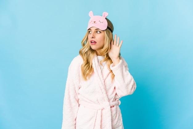 Młoda blondynka ubrana w piżamę próbuje słuchać plotek