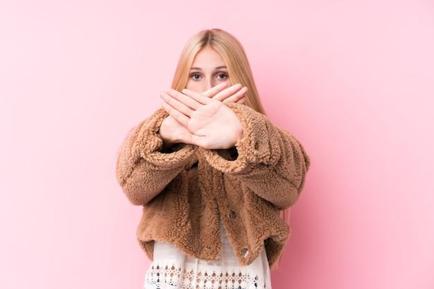 Młoda blondynka ubrana w płaszcz na różowo robi gest odmowy