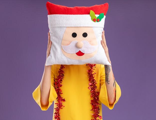 Młoda blondynka ubrana w świąteczny wieniec i girlandę z blichtru na szyi trzymającą poduszkę świętego mikołaja przed twarzą odizolowaną na fioletowej ścianie