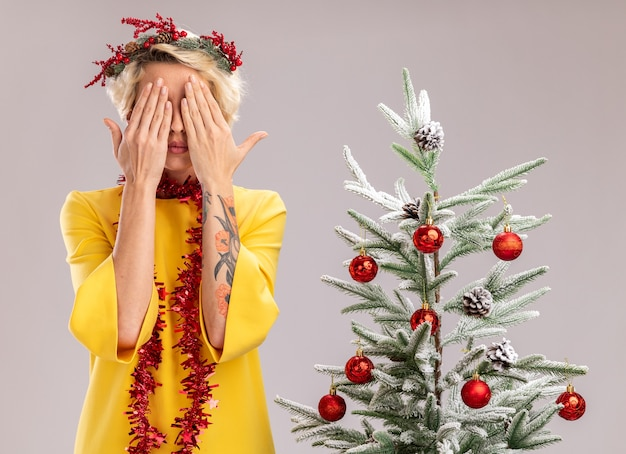 Młoda blondynka ubrana w świąteczny wieniec i girlandę z świecidełek na szyi stojącą w pobliżu ozdobionej choinki zakrywającej oczy rękami na białej ścianie