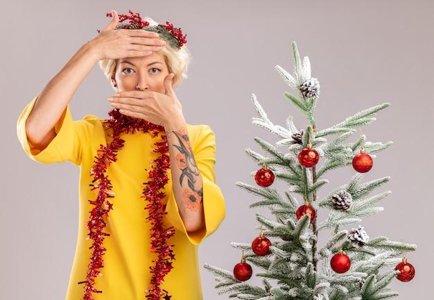 Młoda blondynka ubrana w świąteczny wieniec i girlandę ze świecidełek na szyi stojącą w pobliżu ozdobionej choinki patrzącą trzymając ręce na czole i ustach na białej ścianie