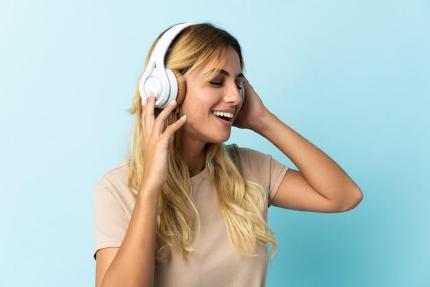 Młoda blondynka urugwajczyk na białym tle na niebieski słuchanie muzyki i śpiewu
