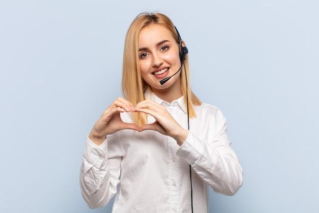 Młoda blondynka uśmiecha się i czuje się szczęśliwa, urocza, romantyczna i zakochana, tworząc kształt serca obiema rękami
