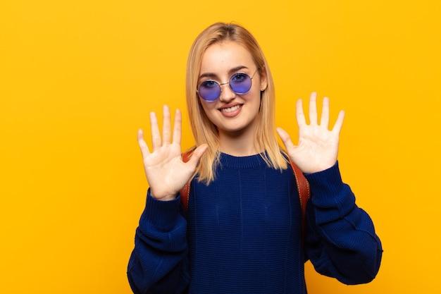 Młoda blondynka uśmiecha się i wygląda przyjaźnie, pokazując cyfrę dziesięć lub dziesiątą ręką do przodu, odliczając w dół