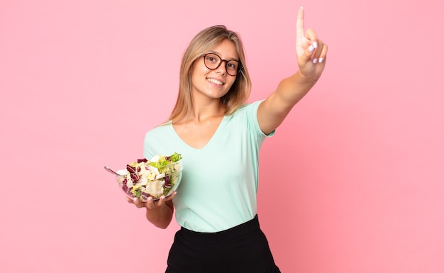 Młoda blondynka uśmiecha się i wygląda przyjaźnie, pokazując numer jeden i trzymając sałatkę