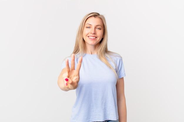 Młoda blondynka uśmiecha się i wygląda przyjaźnie, pokazując numer trzy