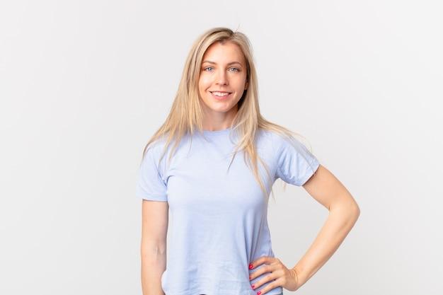 Młoda blondynka uśmiecha się radośnie z ręką na biodrze i pewna siebie