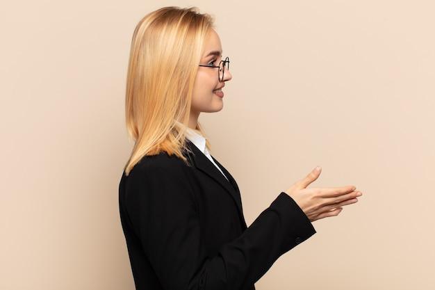 Młoda blondynka uśmiecha się, wita i oferuje uścisk dłoni, aby zamknąć udaną transakcję, koncepcja współpracy