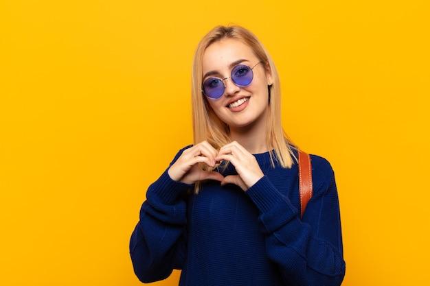 Młoda blondynka uśmiechnięta i czująca się szczęśliwa, słodka, romantyczna i zakochana, co kształt serca obiema rękami