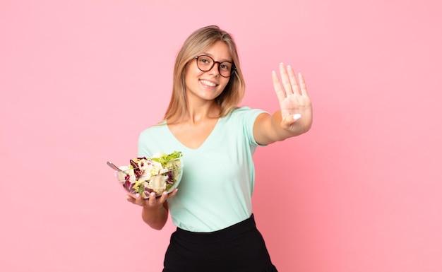 Młoda blondynka uśmiechnięta i wyglądająca przyjaźnie, pokazująca numer cztery i trzymająca sałatkę
