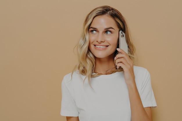 Młoda blondynka uśmiechnięta kobieta za pomocą telefonu komórkowego i patrząc na bok, ciesząc się przyjemną rozmową ze swoim chłopakiem, ubrana w białą koszulkę. nowoczesne technologie i koncepcja komunikacji