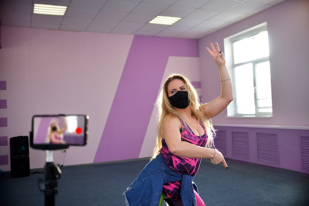 Młoda blondynka w czarnej masce podczas pandemii prowadzi treningi w klubie sportowym.