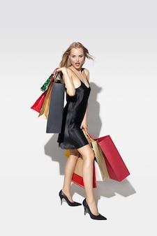 Młoda blondynka w czarnej sukni zakupy na białej ścianie
