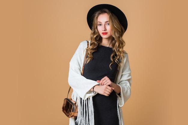 Młoda blondynka w czarnym wełnianym kapeluszu ubrana w duże ponczo z białymi frędzlami i długą szarą sukienkę