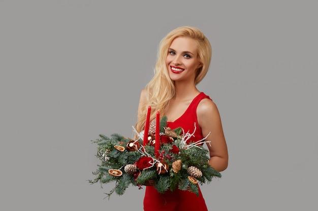 Młoda blondynka w czerwonej sukience trzyma w dłoniach świąteczny wieniec. świąteczny bukiet kwiatów i gałęzi choinki na szarym neutralnym tle