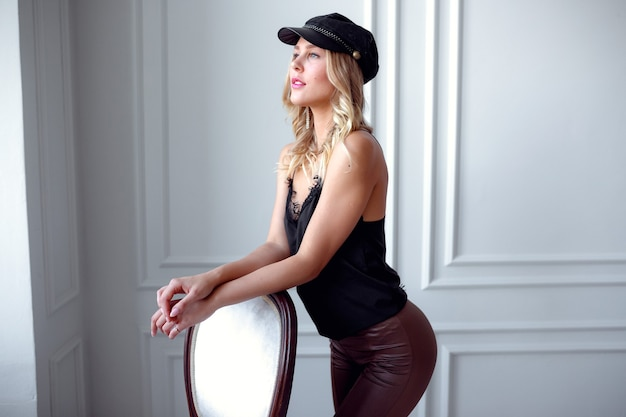 Młoda blondynka w jedwabnej bluzce i skórzanych spodniach pozuje na tle białej ściany. katalog salon piękności impreza. idea i koncepcja zdrowia, młodości i właściwej dbałości o siebie