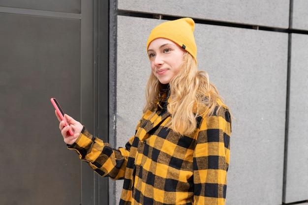 Młoda blondynka w kraciastej koszuli i żółtym kapeluszu