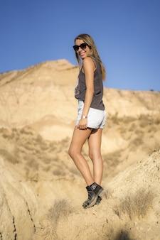 Młoda blondynka w krótkich spodenkach pozuje w pobliżu klifu na pustyni w las bardenas reales, navarra, hiszpania