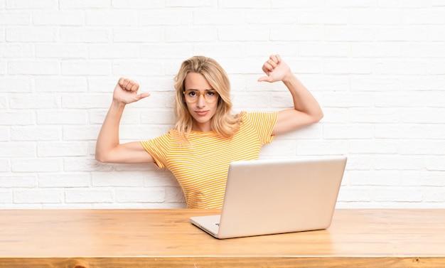 Młoda blondynka w laptopie czuje się dumna i arogancka, wskazując na siebie