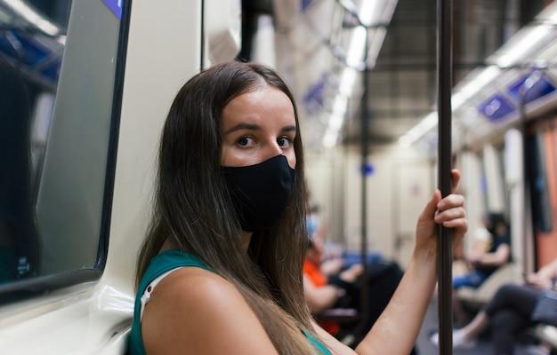 Młoda blondynka w masce ochronnej przed wirusem siedzi na siedzeniu w metrze.
